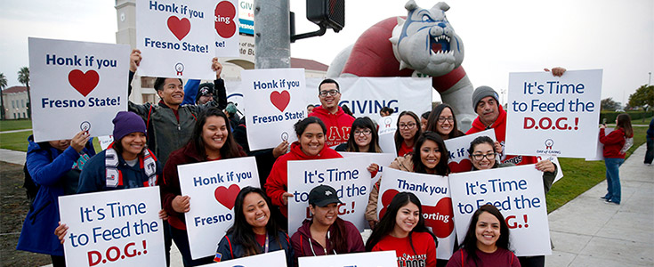Fresno State student volunteers on one of the campus corners holding up Day of Giving signs